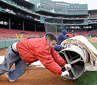 The Fenway Park grounds crew gets the most work as the Rays-Red Sox opener is rained out.  (AP)
