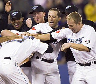 The Blue Jays have a ton of aggressive affection for Jose Bautista after he scores the winning run. (AP)