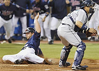 Brian Buscher, the third Twin to draw a walk in the ninth inning, slides in with the winning run.  (AP)