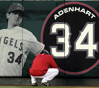 Starting pitcher Jered Weaver pays respect to an image of Nick Adenhart on the outfield wall.  (AP)
