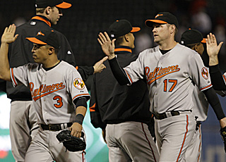 Aubrey Huff (17) finishes with four hits and celebrates with the Orioles after a wild showdown.  (AP)