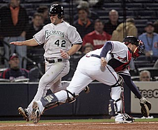 Dan Uggla avoids Atlanta catcher Brian McCann as he scores during Florida's five-run ninth.  (AP)