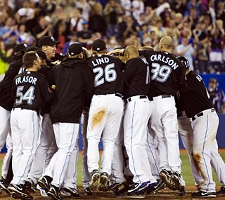 The Blue Jays mob Lyle Overbay at home plate after his winning home run in the 12th inning.  (AP)