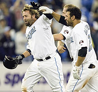 Jose Bautista (right) helps lead the celebration after Kevin Millar delivers the walk-off single.  (AP)