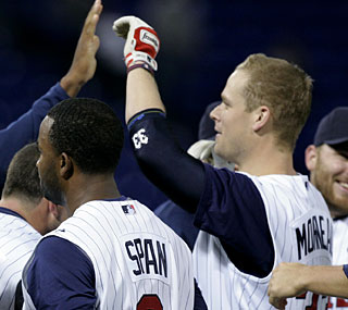 Justin Morneau (right) is not known for his speed, but it comes in handy for the Twins in the ninth.  (AP)