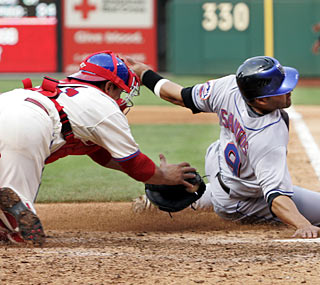 Phillies catcher Carlos Ruiz tags out Omir Santos in the eighth inning on a throw from Jayson Werth.  (AP)