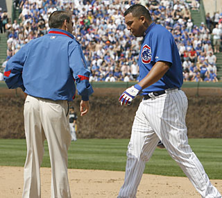 Cubs trainer Mark O'Neal checks on Carlos Zambrano after the pitcher reaches first on a bunt single. (AP)