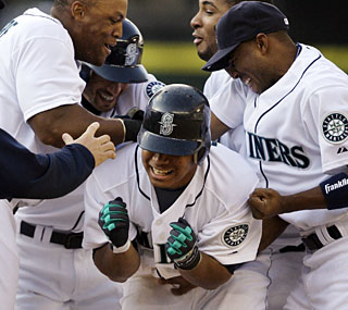 The Mariners mob Jose Lopez after he ends a long day at the ballpark with a bloop single in the 15th.  (AP)