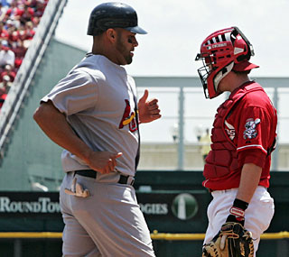 Albert Pujols and the Cardinals outlast a blown save in the ninth to race past the Reds in 10.  (AP)