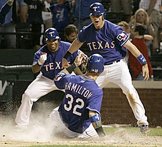 Josh Hamilton scores the winning run, much to the delight of Marlon Byrd (left) and Michael Young.  (AP)