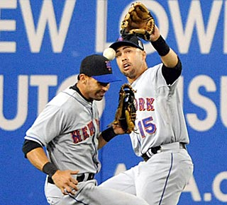 Carlos Beltran (right) calls off Angel Pagan, but the ball falls for a two-base error in the 11th.  (US Presswire)