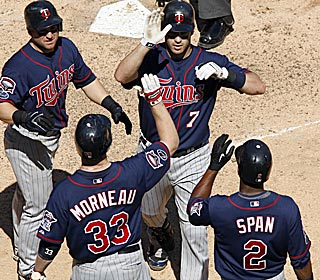 Joe Mauer (7) receives high-fives following his grand slam for four of his six RBI on the day.  (US Presswire)