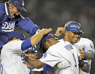 The Dodgers swarm Juan Pierre, who pushes across the winning run in the 10th inning with a bases-loaded walk.  (AP)