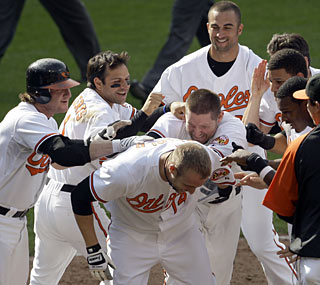 The Orioles greet Nolan Reimold (14) at home plate after his game-winning homer in the 11th inning.   (AP)