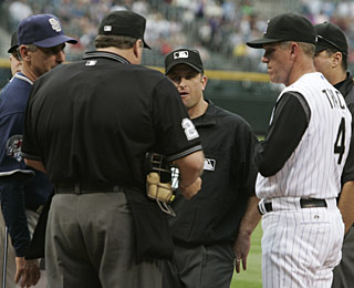 Jim Tracy (right) exchanges lineup cards with Padres manager Bud Black. (AP)