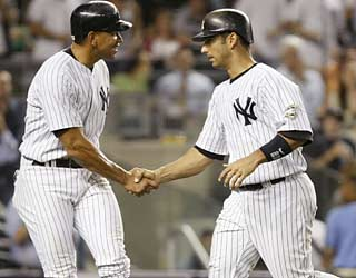 Jorge Posada (right) more than makes up for his error by providing a three-run shot in the sixth inning.  (AP)