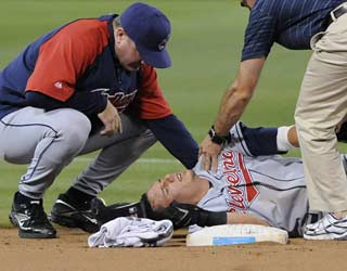 Cleveland's staff checks on Asdrubal Cabrera, who injures his left shoulder sliding into second base.  (AP)