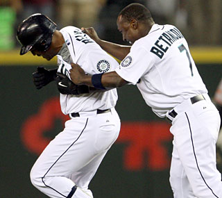 Yuniesky Betancourt (right) congratulates Adrian Beltre after Beltre's game-winning single in the ninth.   (AP)