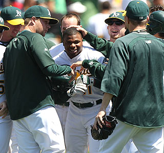 Rajai Davis gets some love from his Oakland teammates following Davis' game-winning single.  (Getty Images)