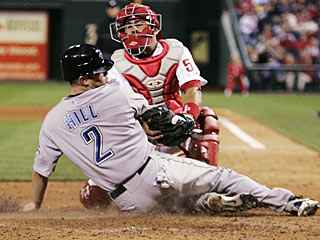 Aaron Hill beats the tag from Carlos Ruiz to score the go-ahead run on Scott Rolen's single. (AP)
