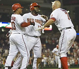 Cristian Guzman is greeted by teammates after scoring in the 11th in the Nationals' third straight win.  (AP)