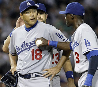 Hiroki Kuroda (18) has to leave one out shy of a complete game, but his teammates appreciate the effort.  (AP)
