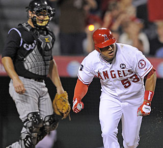 With catcher Chris Iannetta looking on, Bobby Abreu takes off after connecting for a single. (AP)