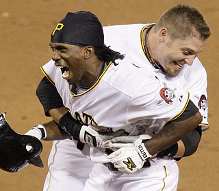 Andrew McCutchen caps the Bucs' rally with a bloop single, earning a hug from Eric Hinske.  (AP)