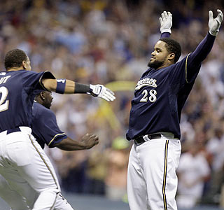 Prince Fielder awaits congratulations from the rest of the Brewers following his game-winning hit.  (AP)
