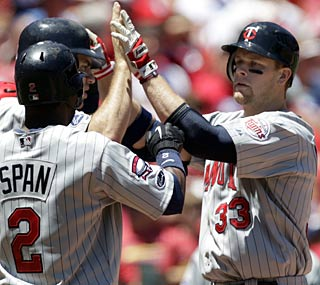 Justin Mornueau (right) gets the Twins started in the first inning with a three-run shot.  (AP)