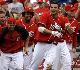 Joey Votto (19) is the hero after his fourth hit of the game -- a bases-loaded, two-out single -- wins it. (AP)