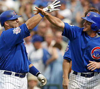 With two outs in the 10th, Jake Fox (left) draws the big walk that scores Ryan Theriot (right).   (US Presswire)
