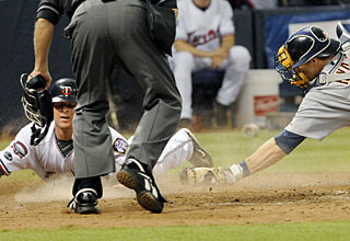 Matt Tolbert beats the tag by catcher Dusty Ryan to score the go-ahead run for Minnesota. (AP)
