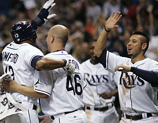 Carl Crawford (13) celebrates with teammates after scoring the winning run on Ben Zobrist's single. (AP)