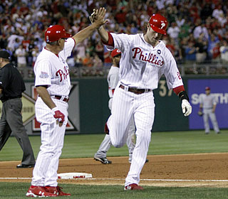 Third-base coach Sam Perlozzo high-fives Jayson Werth, who hits his seventh homer in the last 12 games.  (AP)