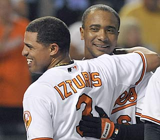 Cesar Izturis greets Melvin Mora, whose first homer in 50 games wins it for the Orioles.  (AP)