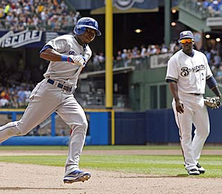 All Bill Hall can do is watch as Orlando Hudson rounds the bases during the first of his two homers.  (AP)