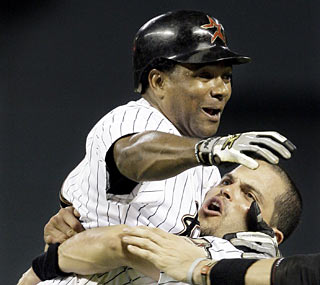 After Miguel Tejada lifts the 'Stros in the ninth, Pudge Rodriguez returns the favor by hoisting up the hero.  (AP)