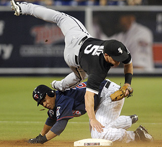 Carlos Gomez breaks up the double play, sending Chicago second baseman Jayson Nix for a tumble.  (AP)