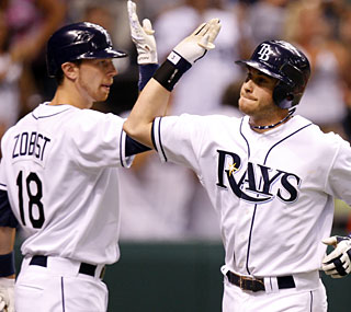 Evan Longoria (right) homers to support Scott Kazmir as the Rays slow down the Yankees.  (AP)