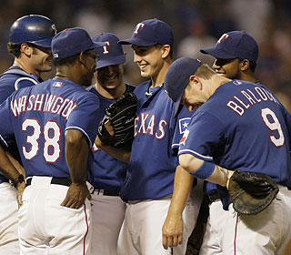 Derek Holland (center) has everyone laughing as he begs Ron Washington to stay in for one more out.  (AP)