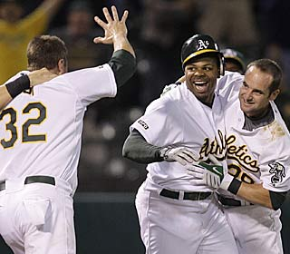 Rajai Davis (middle) is mobbed by teammates after his walk-off triple with two out in the ninth.  (AP)