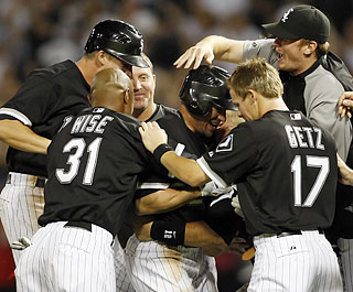 Scott Podsednik (center) is swarmed by teammates after his third walk-off hit of the season.  (US Presswire)
