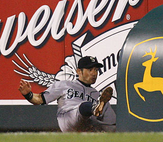 Ichiro Suzuki, who leads off with a homer, makes a sliding catch along the stands for the final out.  (AP)
