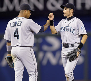 Ichiro nails down his 52nd multihit game of the season while Jose Lopez (left) gets three hits of his own.  (AP)