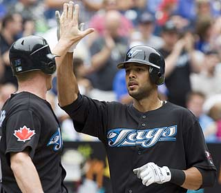 Alex Rios gets some love from his teammate after getting the Jays started with a two-run homer. (AP)