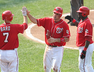 Ryan Zimmerman (11), who goes 3 for 5, scores with Cristian Guzman (right) on an Elijah Dukes double.  (AP)