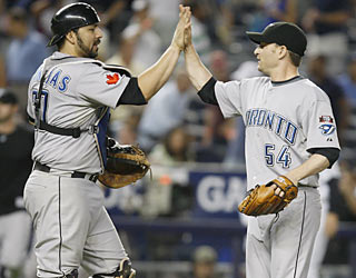 Rod Barajas congratulates Jason Frasor, who shuts down the Yankees' win streak in the ninth inning.  (AP)