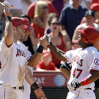 Welcome home: Howie Kendrick (right) is greeted following this three-run blast in the seventh.  (AP)