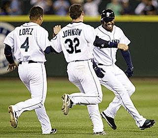 Ken Griffey Jr.'s teammates chase him down after he ends the longest 1-0 game in Mariners history.  (AP)